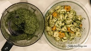 Basil Pesto in bowl on left side; tortellini coated with basil pesto in bowl to right.