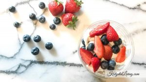 strawberries, blueberries and a finished patriotic trifle cup on marble
