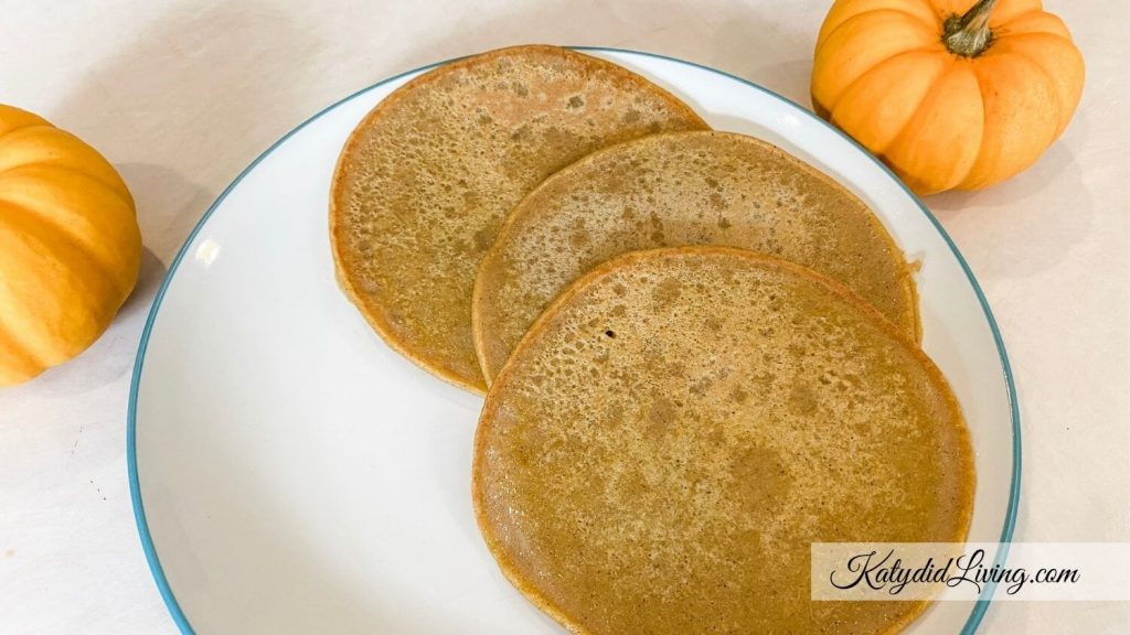 Pumpkin Spice Swedish Pancakes on a plate with mini puumpkins next to the plate.