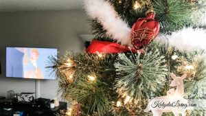 The Ultimate Netflix Christmas Movie Watchlist | Lit Christmas tree with heart and deer ornaments and TV playing movie in background.