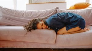 How to Relieve Period Pain - Woman in PJs curled up on couch in pain.