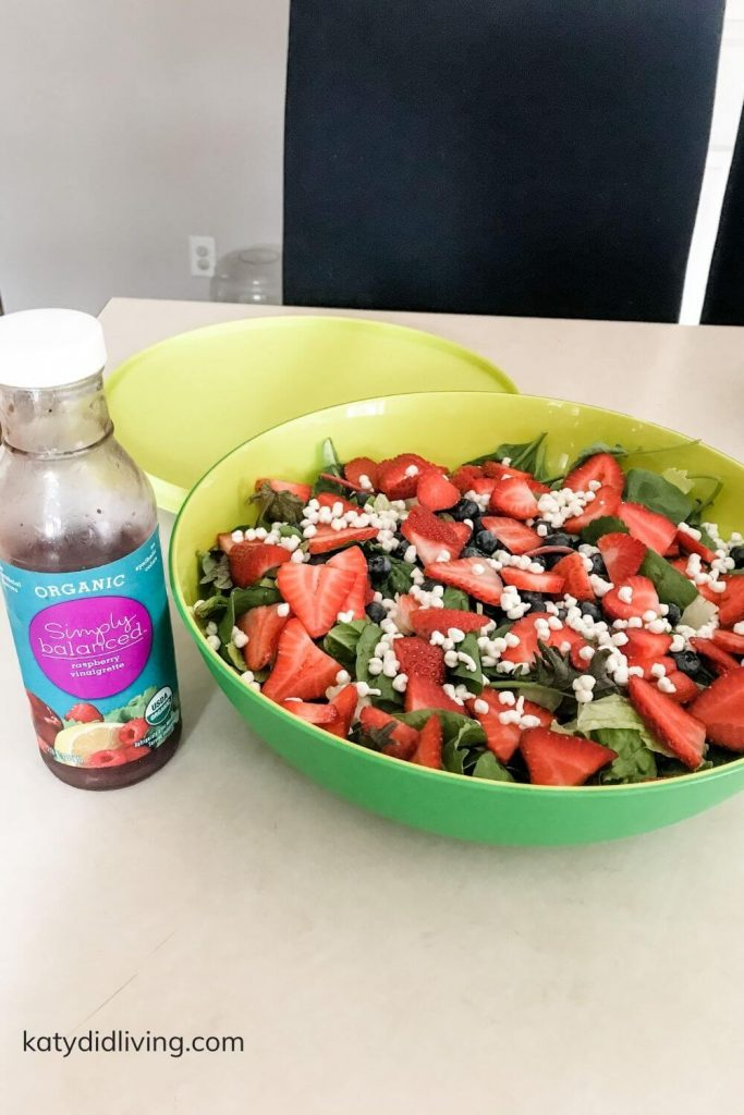Recipe for berry salad- complete salad in large serving bowl with bottle of raspberry vinaigrette next to it.